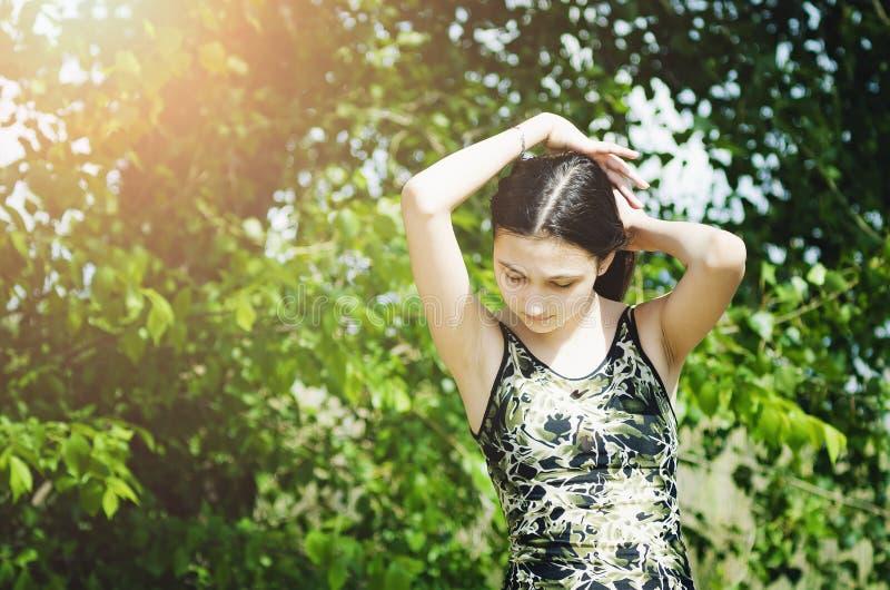 Het mooie tienermeisje op een groene boomachtergrond maakt haar recht royalty-vrije stock foto