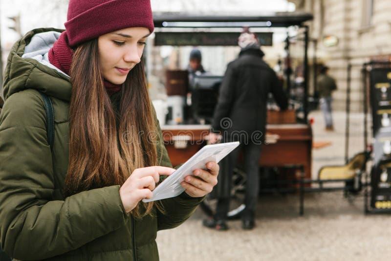 Het mooie toeristenmeisje met een tablet op een straat bekijkt een kaart of gebruikt Internet of een mobiele toepassing royalty-vrije stock afbeelding