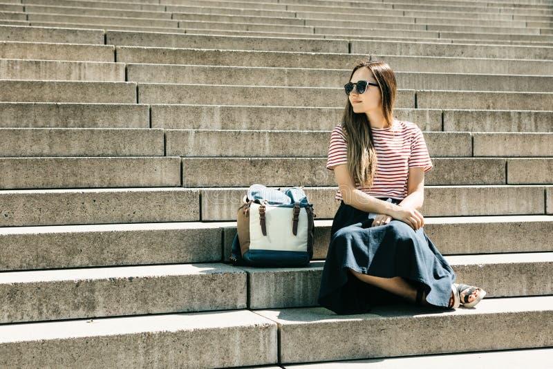 Het mooie toeristenmeisje zit op de treden en de rust royalty-vrije stock fotografie