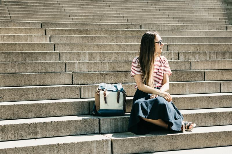 Het mooie toeristenmeisje zit op de treden en de rust royalty-vrije stock foto's