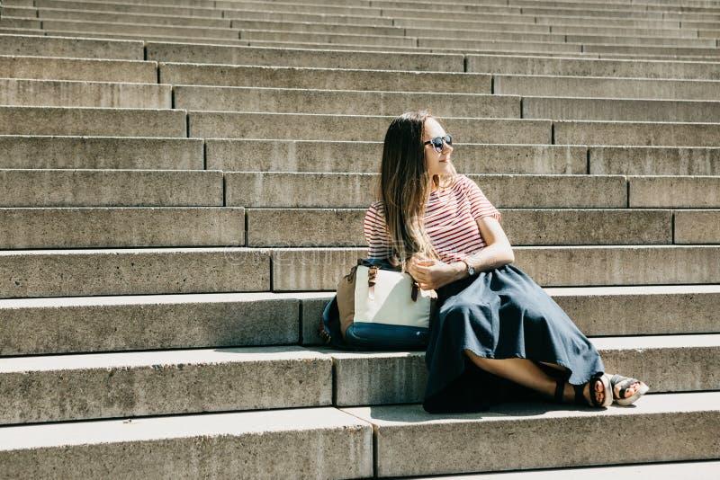Het mooie toeristenmeisje zit op de treden en de rust stock foto