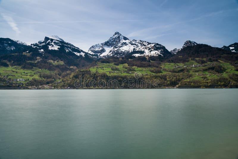 Het mooie turkooise panorama van het bergmeer met snow-covered pieken en groene weiden en bossen stock afbeeldingen