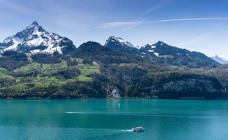 Het mooie turkooise panorama van het bergmeer met snow-covered pieken en groene weiden en bossen en boten op het meer royalty-vrije stock fotografie
