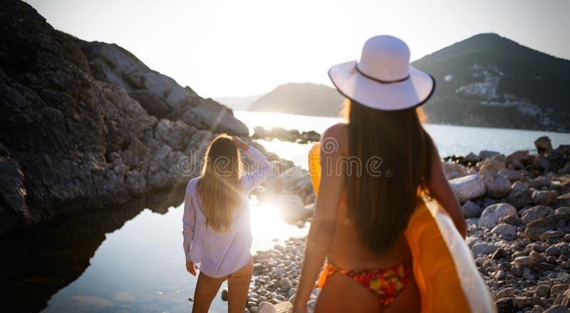 Het mooie vriendenvrouwen genieten die op strand op vakantie lopen stock afbeelding