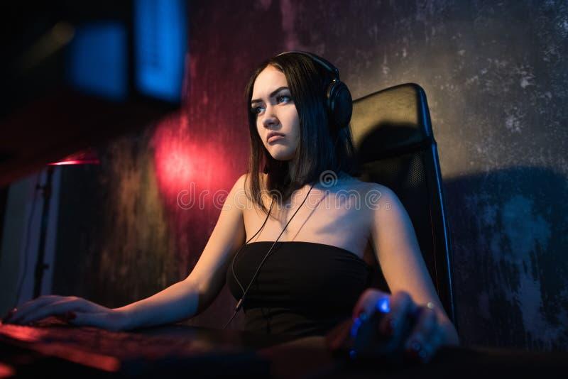 Het mooie Vriendschappelijke Progamer-Meisje doet de stroom van Videospelletjegameplay, die Hoofdtelefoonbesprekingen en Praatjes stock foto