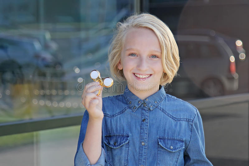 Het mooie vrolijke schoolmeisje spelen met een goud friemelt spinner Een populair in stuk speelgoed stock foto