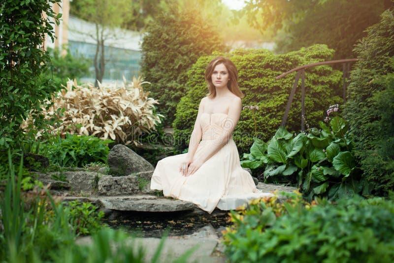 Het mooie vrouw dragen prom kleedt zich in openlucht in Japanse tuin stock fotografie