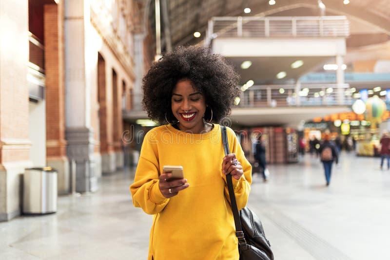 Het mooie vrouw gebruiken mobiel in het station stock foto