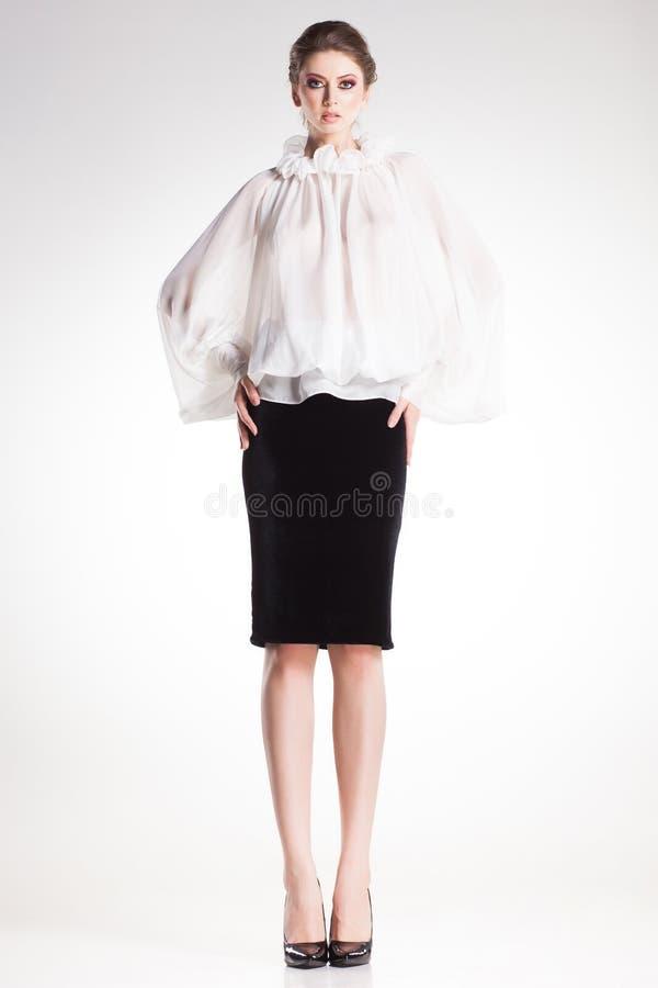 Het mooie vrouw model stellen in elegante witte blouse en zwarte kleding stock afbeeldingen