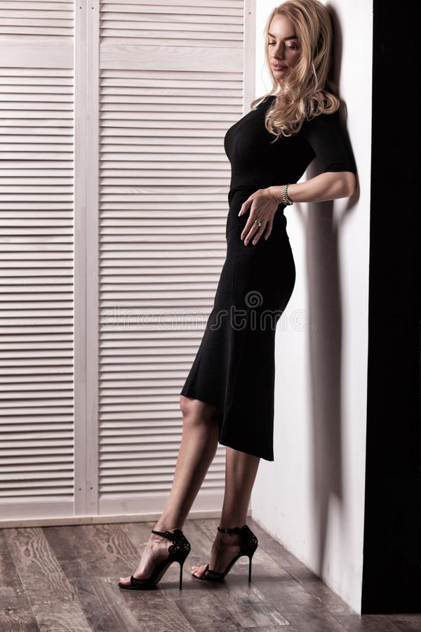 Het mooie vrouw model stellen in elegante zwarte kleding royalty-vrije stock fotografie