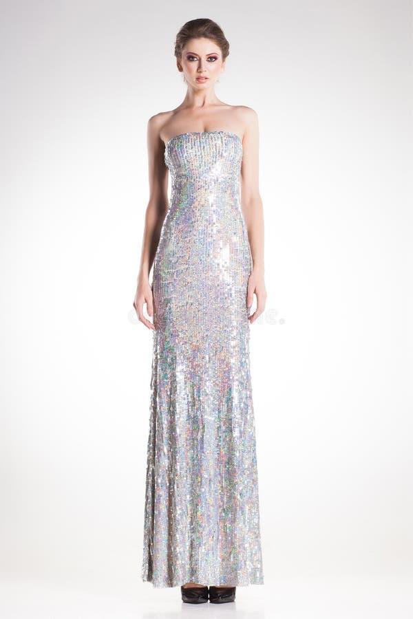 Het mooie vrouw model stellen in lange elegante zilveren lovertjeskleding royalty-vrije stock fotografie