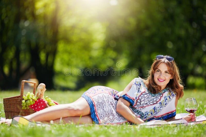 Het mooie vrouw ontspannen bij het park stock fotografie