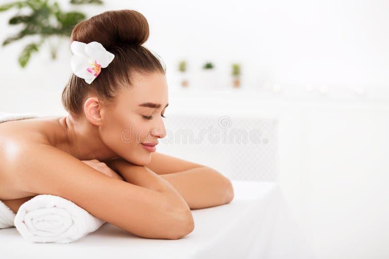 Het mooie vrouw ontspannen bij kuuroordsalon, exemplaarruimte stock afbeeldingen
