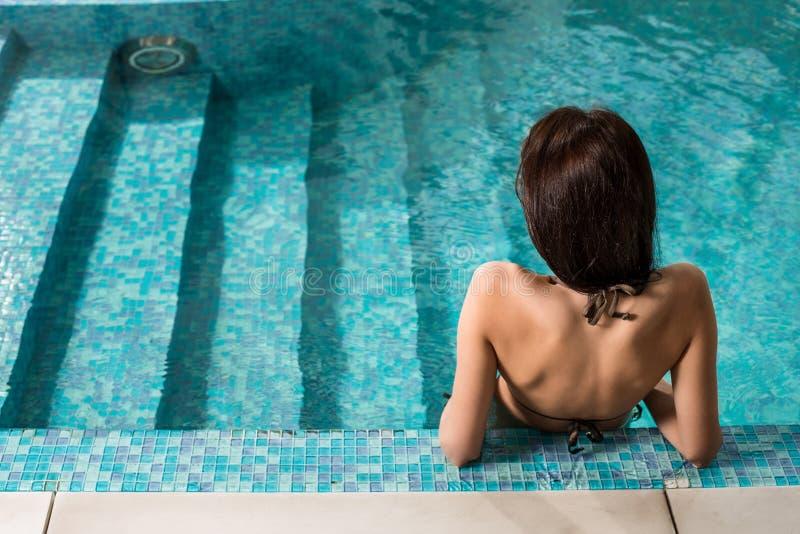 Het mooie vrouw ontspannen bij luxepoolside Meisje bij travel spa toevluchtpool royalty-vrije stock foto
