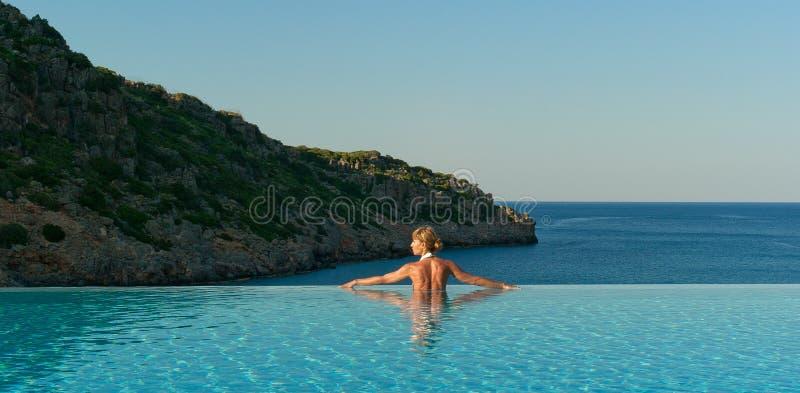 Het mooie vrouw ontspannen in oneindigheids zwembad royalty-vrije stock afbeelding