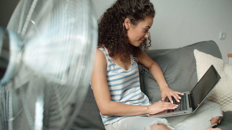 Het mooie vrouw ontspannen op bank die haar laptop thuis in de woonkamer met behulp van royalty-vrije stock foto's