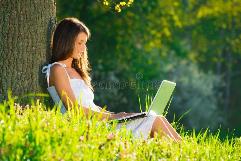 Het mooie vrouw ontspannen op gras met laptop stock fotografie