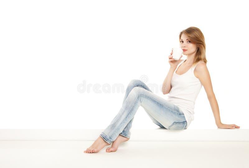 Het mooie vrouw ontspannen thuis en drinkt een koffie stock foto