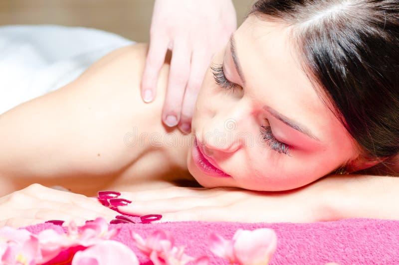 Het mooie vrouw ontspannen tijdens massage met bloemen, perfecte huid royalty-vrije stock fotografie