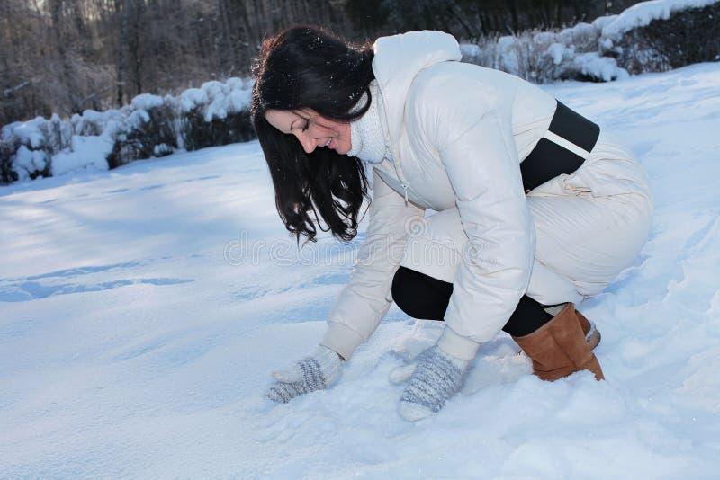 Het mooie vrouw spelen met sneeuw stock foto's