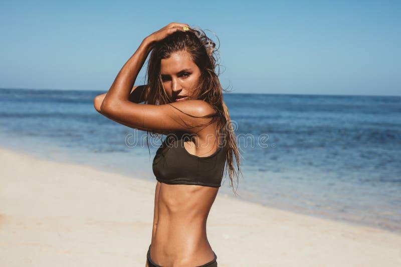 Het mooie vrouw stellen in bikini op het strand royalty-vrije stock afbeeldingen