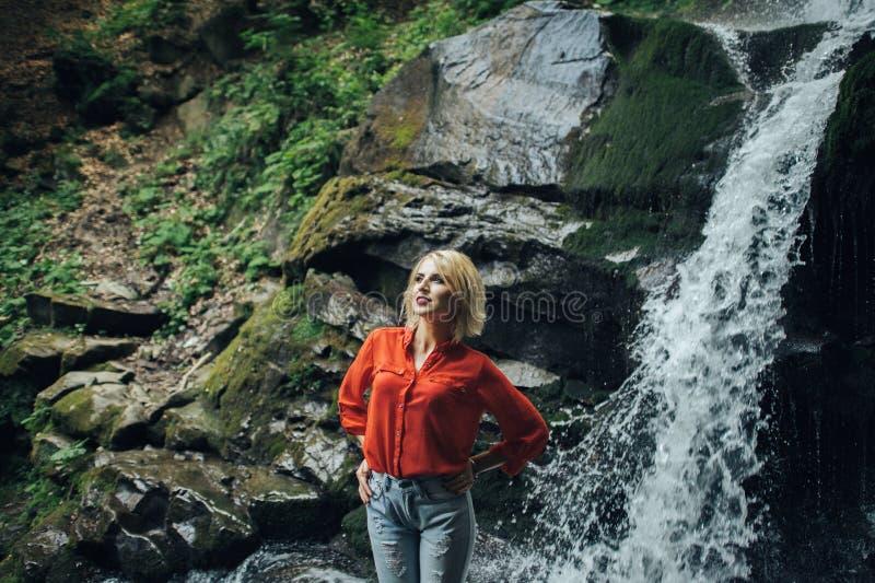 Het mooie vrouw stellen dichtbij waterval stock fotografie