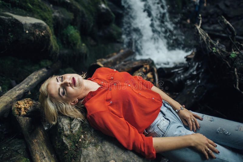 Het mooie vrouw stellen dichtbij waterval royalty-vrije stock foto's