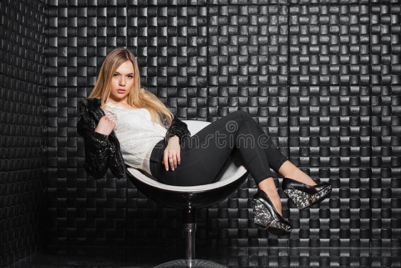 Het mooie vrouw stellen op een stoel stock foto
