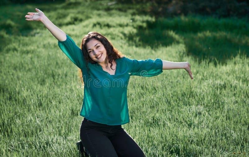 Het mooie vrouw stellen op groen gras bij zonnige dag, de zomer bos, helder landschap met schaduwen royalty-vrije stock afbeeldingen