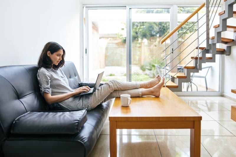 Het mooie vrouw typen op laptop bij modern comfortabel huis stock fotografie