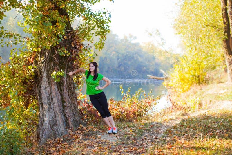 Het mooie vrouw uitrekken die zich dichtbij grote oude boom bevinden royalty-vrije stock foto's