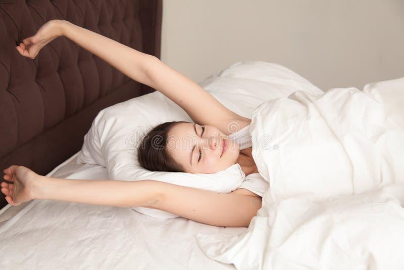 Het mooie vrouw uitrekken zich met genoegen in bed royalty-vrije stock afbeelding
