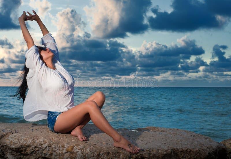 Het mooie vrouw uitrekken zich op een rots door de oceaan bij zonsondergang royalty-vrije stock fotografie