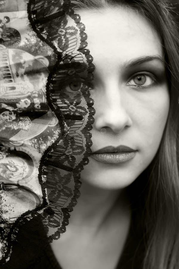 Het mooie vrouw verbergen achter ventilator stock foto