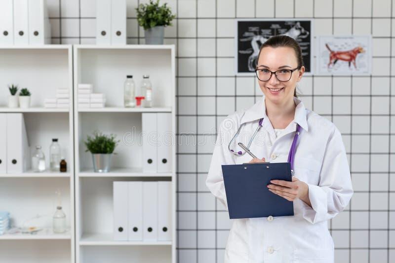 Het mooie vrouw veterinaire glimlachen Veterinaire Kliniek Het houden van een tablet en een pen royalty-vrije stock foto's