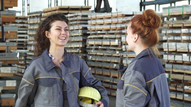 Het mooie vrouwelijke fabrieksarbeider hoge fiving met haar collega stock foto