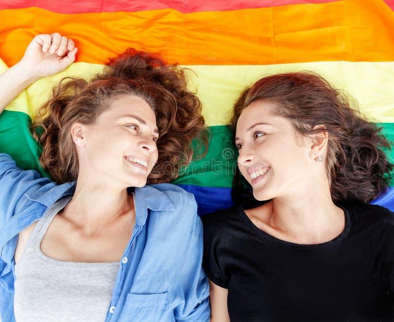 Het mooie vrouwelijke jonge lesbische paar in liefde ligt op de regenboogvlag, symbool van de lgbt communautaire, gelijke rechten stock afbeelding