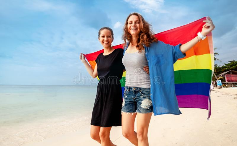 Het mooie vrouwelijke jonge lesbische paar in liefde loopt langs het strand met een regenboogvlag, symbool van de LGBT-gemeenscha stock afbeeldingen
