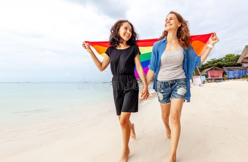 Het mooie vrouwelijke jonge lesbische paar in liefde loopt langs het strand met een regenboogvlag, symbool van de LGBT-gemeenscha royalty-vrije stock foto's