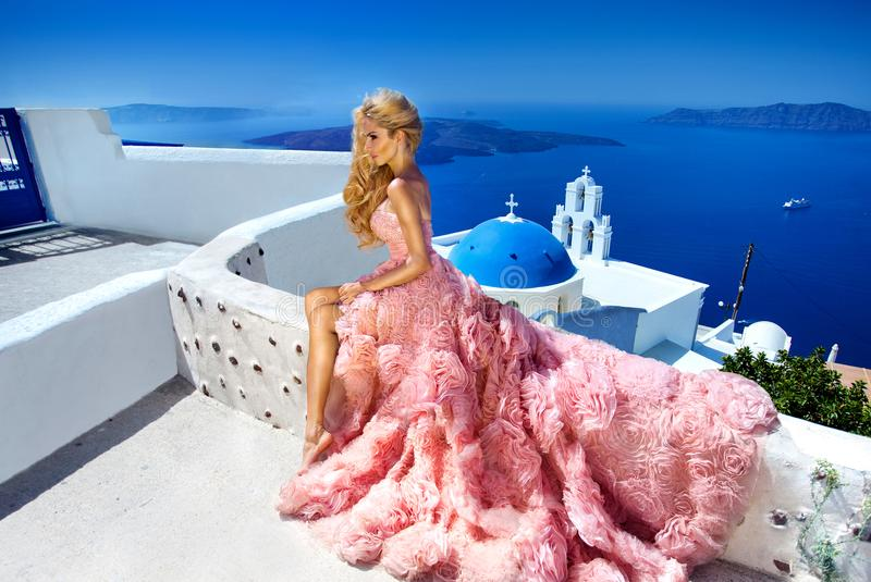 Het mooie vrouwelijke model van het bruidblonde in verbazende huwelijkskleding stelt op het Eiland Santorini in Griekenland stock foto's