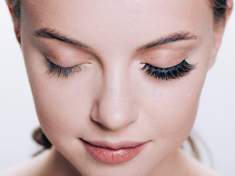 Het mooie vrouwengezicht met wimpers geselt uitbreiding before and after natuurlijke make-up gesloten ogen van de schoonheids de  royalty-vrije stock fotografie