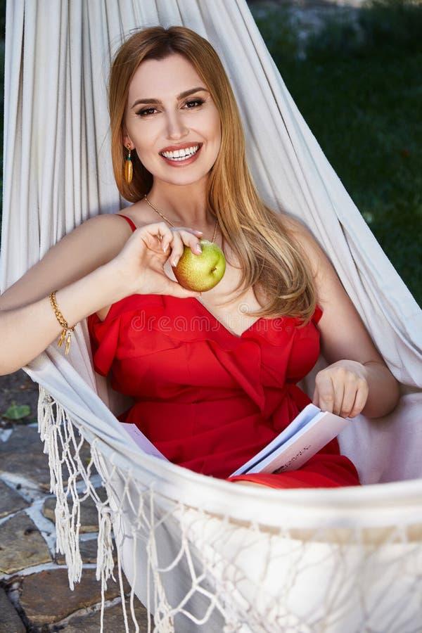 Het mooie vrouwenmodel met lang blond haar ligt in een hangmat rel stock fotografie