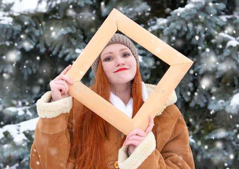 Het mooie vrouwenportret op de winter openlucht, kijkt door houten kader, sneeuwsparren in bos, lang rood haar, die een sheepsk d royalty-vrije stock afbeelding