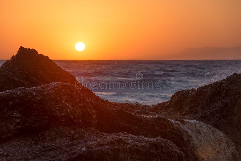 Het mooie warme zonsondergang lichte gloeien over een rotsachtig tropisch strand stock foto
