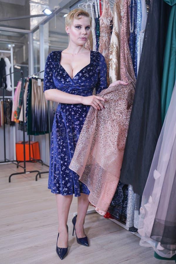 Het mooie weelderige meisje in een modieuze kleding die in de opslag lopen en kiest nieuwe kleren, binnen bekijkend in kostuums o stock fotografie