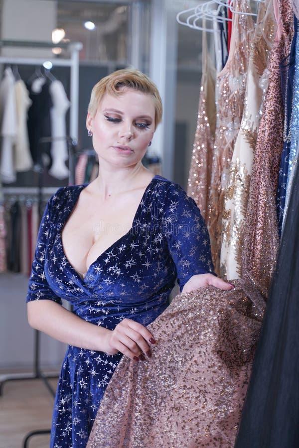 Het mooie weelderige meisje in een modieuze kleding die in de opslag lopen en kiest nieuwe kleren, binnen bekijkend in kostuums o stock foto