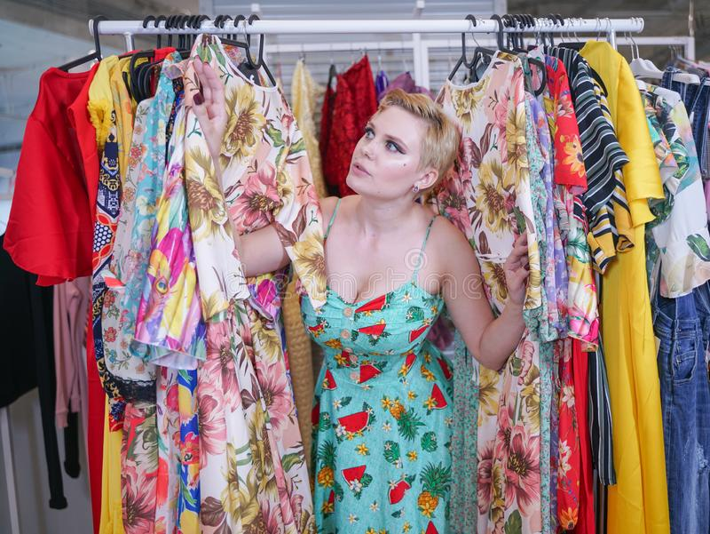 Het mooie weelderige meisje in een modieuze kleding die in de opslag lopen en kiest nieuwe kleren, binnen bekijkend in kostuums o stock afbeelding