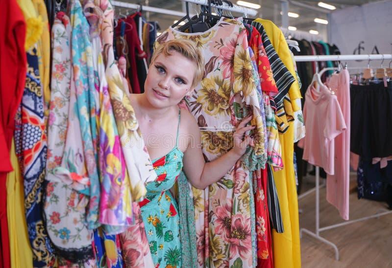 Het mooie weelderige meisje in een modieuze kleding die in de opslag lopen en kiest nieuwe kleren, binnen bekijkend in kostuums o royalty-vrije stock afbeelding