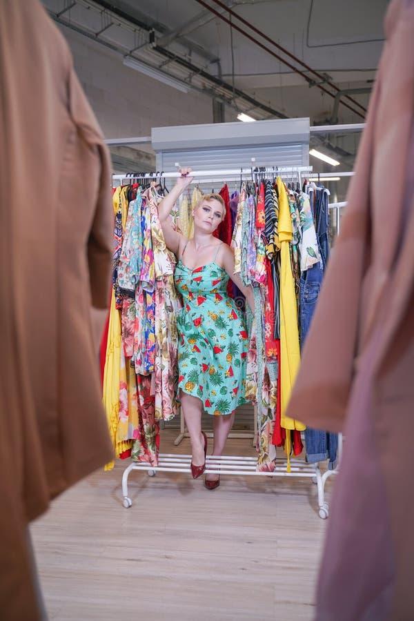 Het mooie weelderige meisje in een modieuze kleding die in de opslag lopen en kiest nieuwe kleren, binnen bekijkend in kostuums o stock afbeeldingen