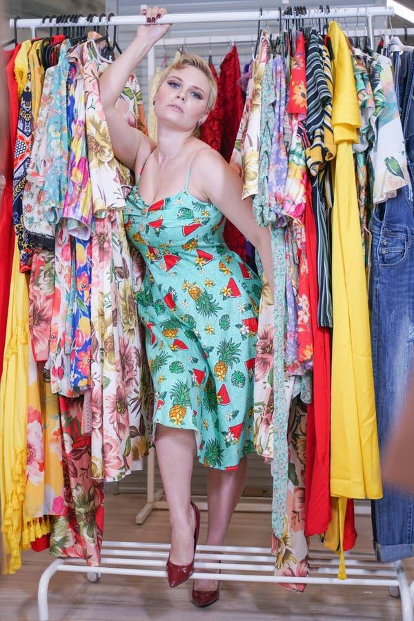 Het mooie weelderige meisje in een modieuze kleding die in de opslag lopen en kiest nieuwe kleren, binnen bekijkend in kostuums o stock foto's
